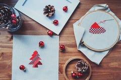 Διαγώνια σχέδια και διακοσμήσεις βελονιών Χριστουγέννων στον ξύλινο πίνακα Προετοιμασία των χειροποίητων δώρων για το νέα έτος κα Στοκ Φωτογραφίες