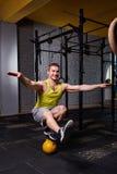 Διαγώνιο κατάλληλο άτομο ικανότητας που στέκεται σε μια πόδι και ισορροπία στα kettlebells στη γυμναστική ενάντια στο τουβλότοιχο Στοκ φωτογραφίες με δικαίωμα ελεύθερης χρήσης