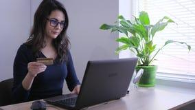 Διαδίκτυο που ψωνίζει, επιχειρησιακή κυρία με την πιστωτική κάρτα καθιστά τη σε απευθείας σύνδεση πληρωμή μέσω του lap-top στην α απόθεμα βίντεο