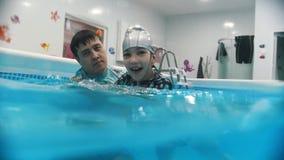 Διαδικασία αποκατάστασης νερού με το παιδί με την εγκεφαλική παράλυση Ένα χαμογελώντας παιδί προκύπτει από το νερό απόθεμα βίντεο