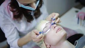 Διαδικασία επέκτασης Eyelash Μάτι γυναικών με τα μακροχρόνια eyelashes Τα μαστίγια, Beautician και η νέα γυναίκα σε ένα σαλόνι ομ απόθεμα βίντεο