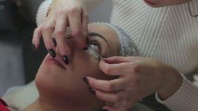 Διαδικασία επέκτασης Eyelash Μάτι γυναικών με τα μακροχρόνια eyelashes φιλμ μικρού μήκους