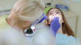Διαδικασία επεξεργασίας δοντιών στο γραφείο οδοντιάτρων Ξανθός οδοντίατρος που συνεργάζεται με τον ασθενή φιλμ μικρού μήκους
