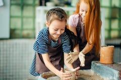 Διαδικασία εργασίας με τη ρόδα αγγειοπλαστών αργίλου Δύο κορίτσια που κάνουν την αγγειοπλαστική στο στούντιο Στοκ Φωτογραφία