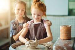 Διαδικασία εργασίας με τη ρόδα αγγειοπλαστών αργίλου Δύο κορίτσια που κάνουν την αγγειοπλαστική στο στούντιο Στοκ εικόνα με δικαίωμα ελεύθερης χρήσης