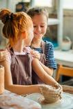 Διαδικασία εργασίας με τη ρόδα αγγειοπλαστών αργίλου Δύο κορίτσια που κάνουν την αγγειοπλαστική στο στούντιο Στοκ Εικόνα