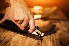 Διαδικασία εργασίας της ζώνης δέρματος στο εργαστήριο δέρματος Εργαλείο εκμετάλλευσης ατόμων Βυρσοδέψης στον παλαιό φλοιό πίνακας Στοκ φωτογραφία με δικαίωμα ελεύθερης χρήσης