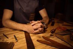 Διαδικασία εργασίας της ζώνης δέρματος στο εργαστήριο δέρματος Χέρια εκμετάλλευσης ατόμων στον ξύλινο πίνακα Επεξεργαμένος τα εργ Στοκ Εικόνα