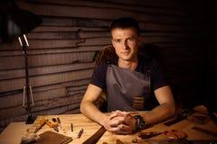 Διαδικασία εργασίας της ζώνης δέρματος στο εργαστήριο δέρματος Χέρια εκμετάλλευσης ατόμων στον ξύλινο πίνακα Επεξεργαμένος τα εργ Στοκ φωτογραφία με δικαίωμα ελεύθερης χρήσης