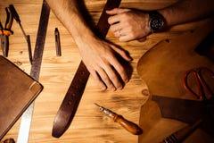 Διαδικασία εργασίας της ζώνης δέρματος στο εργαστήριο δέρματος Χέρια εκμετάλλευσης ατόμων στον ξύλινο πίνακα Επεξεργαμένος τα εργ Στοκ εικόνες με δικαίωμα ελεύθερης χρήσης