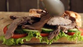 Διαδικασία μαγειρέματος που κατασκευάζει το σάντουιτς βόειου κρέατος ψητού με τη σαλάτα αγγουριών ντοματών φιλμ μικρού μήκους