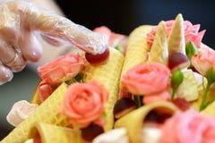 Διαδικασία μια όμορφη ανθοδέσμη που αποτελείται από τα ρόδινα τριαντάφυλλα και τα διάφορα γλυκά Στοκ φωτογραφία με δικαίωμα ελεύθερης χρήσης