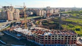 Διαδικασία οικοδόμησης σε ένα εργοτάξιο οικοδομής Οι γερανοί στηρίζονται τα καινούργια σπίτια στα περίχωρα πόλεων απόθεμα βίντεο