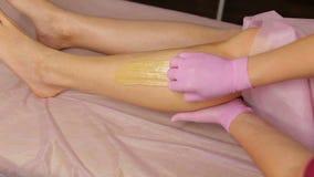 Διαδικασία της τρίχας που μεταθέτει στα πόδια σε μια όμορφη γυναίκα Γλυκασμός απόθεμα βίντεο
