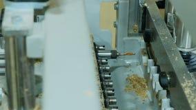 Διαδικασία τις τρύπες στις λεπτομέρειες των ξύλινων επίπλων σε μια σύγχρονη μηχανή διατρήσεων με τρυπάνι φιλμ μικρού μήκους