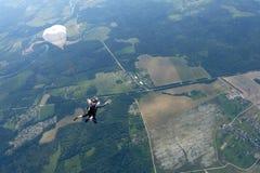 Διαδοχική ελεύθερη πτώση με αλεξίπτωτο Δύο τύποι εμπίπτουν στον ουρανό στοκ εικόνες