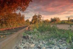 Διαδρομές και σύννεφα σιδηροδρόμου στο ηλιοβασίλεμα Στοκ Φωτογραφίες