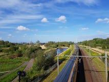 Διαδρομή σιδηροδρόμων και επιταχυνόμενο τραίνο με την αποζημίωση φύσης και ανεμοστρόβιλοι που παράγουν την πράσινη ενέργεια στοκ εικόνα με δικαίωμα ελεύθερης χρήσης