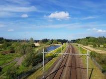 Διαδρομή σιδηροδρόμων με την αποζημίωση φύσης και ανεμοστρόβιλοι που παράγουν την πράσινη ενέργεια στοκ εικόνες