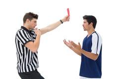 Διαιτητής που παρουσιάζει κόκκινη κάρτα στο ποδοσφαιριστή Στοκ Εικόνες