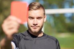 Διαιτητής στο αγωνιστικό χώρο ποδοσφαίρου που παρουσιάζει κόκκινη κάρτα Στοκ Εικόνα