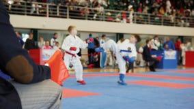 Διαιτητής των πολεμικών τεχνών - karate παιδιών κρατά τις κόκκινες και μπλε σημαίες απόθεμα βίντεο
