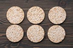 Διαιτητικά στρογγυλά κέικ ρυζιού σε ένα σκοτεινό ξύλινο υπόβαθρο στοκ φωτογραφίες