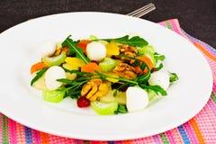 Διαιτητική εύγευστη σαλάτα στο άσπρο πιάτο Arugula, ισοτιμία, ξύλο καρυδιάς α Στοκ Φωτογραφία