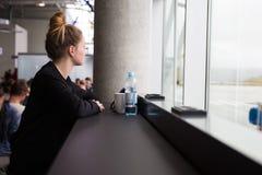 Διακινούμενη γυναίκα που περιμένει στον αερολιμένα και που φαίνεται έξω το παράθυρο στοκ φωτογραφία