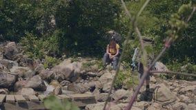 Διακινούμενη γυναίκα που περπατά στην ξύλινη γέφυρα πέρα από τον πετρώδη ποταμό στα βουνά απόθεμα βίντεο