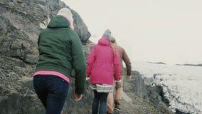 Διακινούμενοι άνδρες και γυναίκες που περπατούν μέσω του βουνού, που μαζί κοντά στη λιμνοθάλασσα πάγου Vatnajokull στην Ισλανδία φιλμ μικρού μήκους