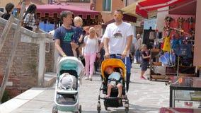 Διακινούμενος με τα παιδιά, πατέρες με τους περιπατητές μωρών που περπατούν μέσω των στενών οδών κατά τη διάρκεια ενός Σαββατοκύρ απόθεμα βίντεο
