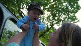 Διακινούμενος με το παιδί, mom γελώντας και χαμογελώντας με το γιο στα χέρια στα πράσινα δέντρα υποβάθρου στο backlight απόθεμα βίντεο