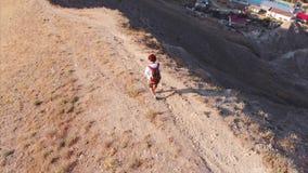 Διακινούμενο άτομο με ένα σακίδιο πλάτης και μια κάμερα, που περπατά μέσω των βουνών, με μια μεγάλη άποψη των βουνών και απόθεμα βίντεο