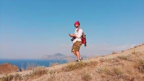 Διακινούμενο άτομο με ένα σακίδιο πλάτης και μια κάμερα, που περπατά μέσω των βουνών, με μια μεγάλη άποψη των βουνών και φιλμ μικρού μήκους