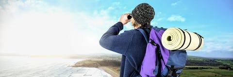 Διακινούμενο άτομο με τις διόπτρες και τσάντα μπροστά από το τοπίο θάλασσας στοκ φωτογραφίες