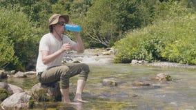 Διακινούμενο άτομο που παίρνει το μπουκάλι νερό από τον ποταμό βουνών στη θερινή αναρρίχηση απόθεμα βίντεο