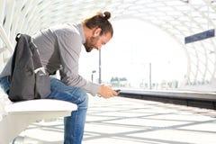 Διακινούμενο άτομο που περιμένει με το τηλέφωνο κυττάρων στην πλατφόρμα τραίνων Στοκ εικόνα με δικαίωμα ελεύθερης χρήσης