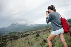 Διακινούμενο κορίτσι που παίρνει τη φωτογραφία του ηφαιστείου στις άγρια περιοχές στοκ εικόνες