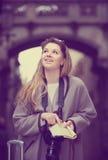 Διακινούμενο κορίτσι που ψάχνει για την κατεύθυνση που χρησιμοποιεί ένα βιβλιάριο στο θόριο Στοκ εικόνα με δικαίωμα ελεύθερης χρήσης