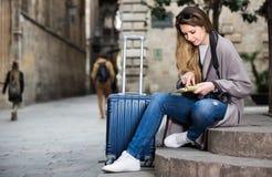 Διακινούμενο κορίτσι που ψάχνει για την κατεύθυνση που χρησιμοποιεί ένα βιβλιάριο στο θόριο Στοκ φωτογραφία με δικαίωμα ελεύθερης χρήσης