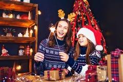 Διακοπές, έννοια οικογενειών και ανθρώπων Ευτυχή μητέρα και μικρό κορίτσι στο καπέλο αρωγών santa με τα sparklers στα χέρια, δώρο στοκ φωτογραφία με δικαίωμα ελεύθερης χρήσης