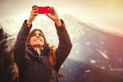 Διακοπές βουνών Ευτυχής γυναίκα που παίρνει μια εικόνα με ένα τηλέφωνο κυττάρων Στοκ Εικόνες