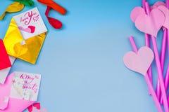 Διακοπές ημέρας βαλεντίνων φωτεινά ρόδινα και μπλε άχυρα κατανάλωσης με τις καρδιές, τους φακέλους και μια ρόδινη κορδέλλα στο μπ Στοκ Εικόνες