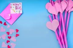 Διακοπές ημέρας βαλεντίνων φωτεινά ρόδινα και μπλε άχυρα κατανάλωσης με τις καρδιές, τους φακέλους και μια ρόδινη κορδέλλα στο μπ Στοκ Φωτογραφίες