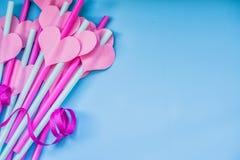 Διακοπές ημέρας βαλεντίνων φωτεινά ρόδινα και μπλε άχυρα κατανάλωσης με τις καρδιές και μια ρόδινη κορδέλλα στο μπλε φωτεινά ρουφ Στοκ Εικόνες