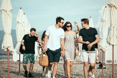 διακοπές, διακοπές η ομάδα φίλων που έχουν τη διασκέδαση στην παραλία, που περπατά, πίνει την μπύρα, το χαμόγελο και το αγκάλιασμ στοκ εικόνα με δικαίωμα ελεύθερης χρήσης