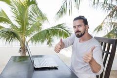 Διακοπές και τεχνολογία Εργασία και ταξίδι Νέο γενειοφόρο άτομο που χρησιμοποιεί το φορητό προσωπικό υπολογιστή καθμένος στο φραγ στοκ φωτογραφία
