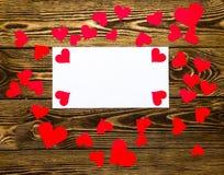 Διακοπές/ρομαντικός/γάμος/υπόβαθρο ημέρας βαλεντίνων με τις μικρές κόκκινες καρδιές εγγράφου και την κενή κάρτα μηνυμάτων Στοκ Εικόνες