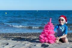 Διακοπές Χριστουγέννων Ένα χαριτωμένο παιδί που φορά ένα καπέλο Santa στην παραλία με ένα ρόδινο χριστουγεννιάτικο δέντρο στοκ φωτογραφία με δικαίωμα ελεύθερης χρήσης